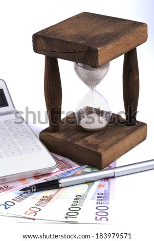 Different euro banknotes with hourglass white calculator and silver fountain pen on white background - stock photo