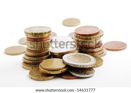 Different euro cents are stacked up in some columns in the middle of hard cash. - stock photo