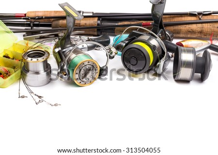 different fishing tackles - rod, reel, line and lures on white background