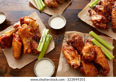 different flavored chicken wings with ranch dipping sauce and celery sticks on wooden table - stock photo