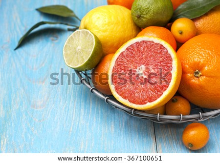 Different fresh citrus fruit in a basket on a blue wooden background - stock photo