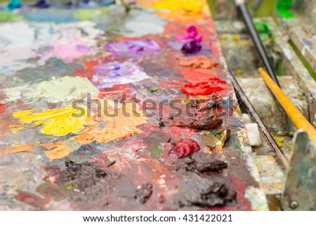 Different fresh oil paint on a bright milticolored palette with professional paintbrushes - stock photo