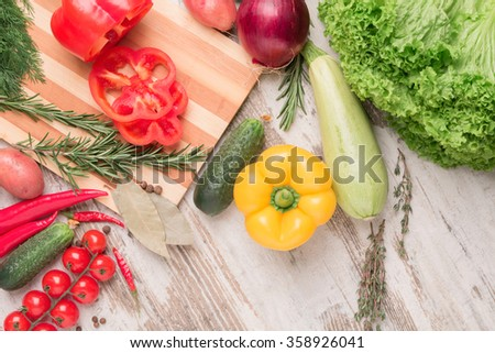 Different fresh vegetables separately on a wooden background cherry tomato pepper chilli, cucumber , rosemary , zucchini , onion , spices , lettuce - stock photo