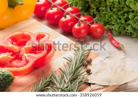Different fresh vegetables separately on a wooden background cherry tomato pepper chilli, cucumber , rosemary , onion , spices , lettuce - stock photo