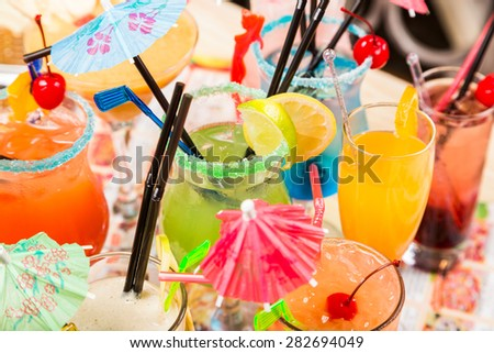 different freshness cocktails with ice in glasses with drinking straw and umbrellas