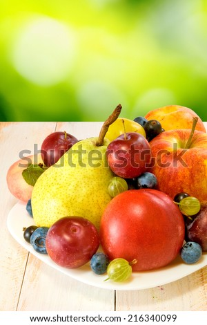 different fruits on a plate on a green background - stock photo