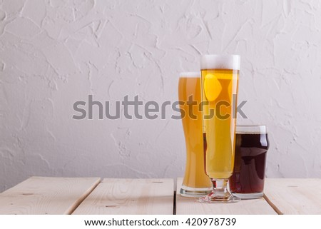 Different glasses of different beer types on light wood table - stock photo