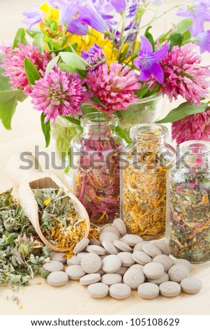 different healing herbs in glass bottles, flowers bouqet, tablets, herbal medicine - stock photo