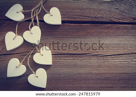 different  hearts hanging in front of wooden board for valentines day - stock photo