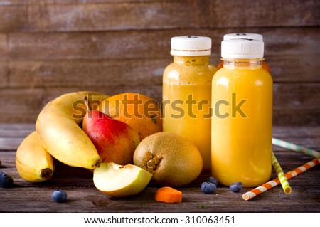 Different juices and fruits on wooden table on background - stock photo