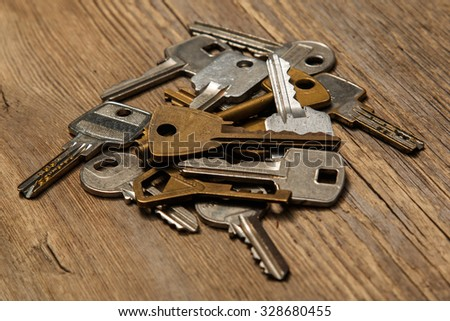 Different keys on wooden background - stock photo