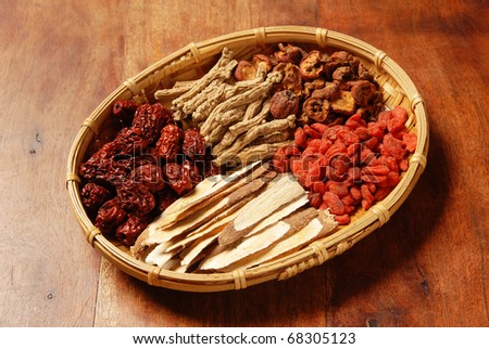 Different kind of Chinese herbal medicine on wicker baskets - stock photo
