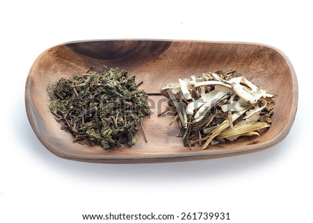 Different kind of Chinese herbal medicine on wooden plate - stock photo