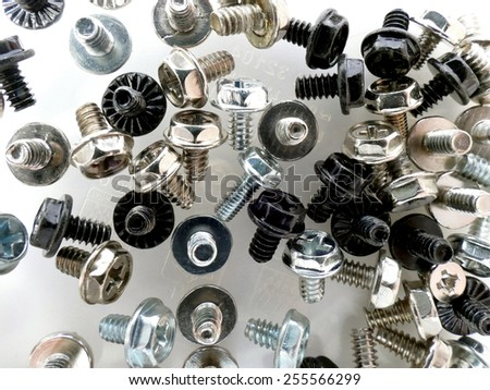 Different kind of computer screws black, brass, chrome close up on semi transparent background - stock photo