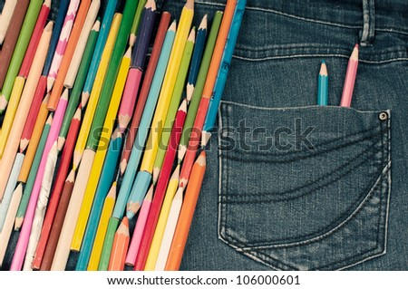 Different kind of pencils on the jeans texture