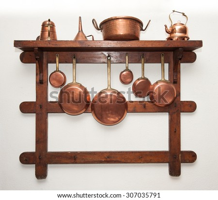 Different kind of vintage copper cookware, pans, coffee pot and funnell hung on wooden shelf in kitchen - stock photo
