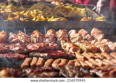 Different kind on grilled meat and sausages with smoke and steam from the grill  - stock photo