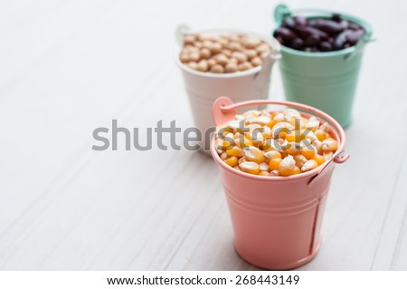 Different kinds of bean seeds, lentil, peas in dish on wooden table, macrobiotic food or healthy food - stock photo