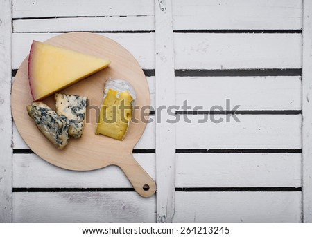 Different kinds of cheese on a light wooden background - stock photo