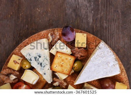 Different kinds of cheese on wooden background - stock photo