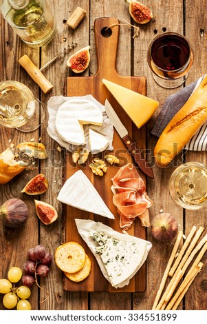 Different kinds of cheeses, wine, baguette, fruits and snacks on rustic wooden table from above. French tasting party or feast scenery. - stock photo