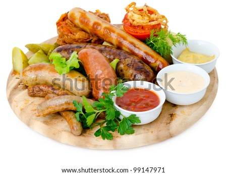 different kinds of grilled sausages with different sauces - stock photo