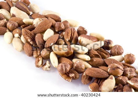 Different kinds of nuts in diagonal line; isolated on white. - stock photo