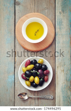 Different kinds of olives on plate with olive oil on wooden background - stock photo