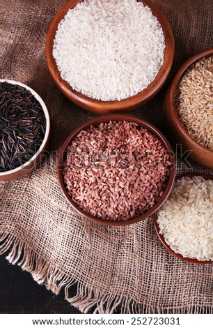 Different kinds of rice in bowls on sackcloth background - stock photo