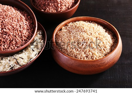 Different kinds of rice in bowls on wooden background - stock photo
