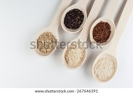 Different kinds of rice in spoons isolated on white background. top view  - stock photo