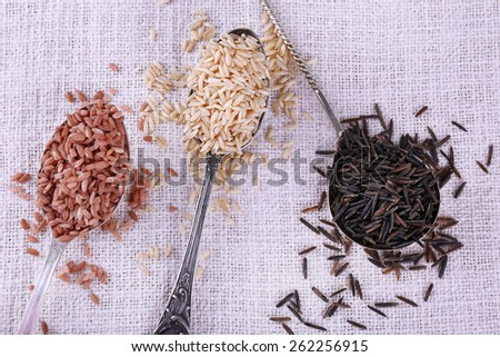 Different kinds of rice in spoons on fabric background - stock photo