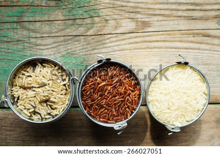 Different kinds of rice in the pots on the rustic table - stock photo