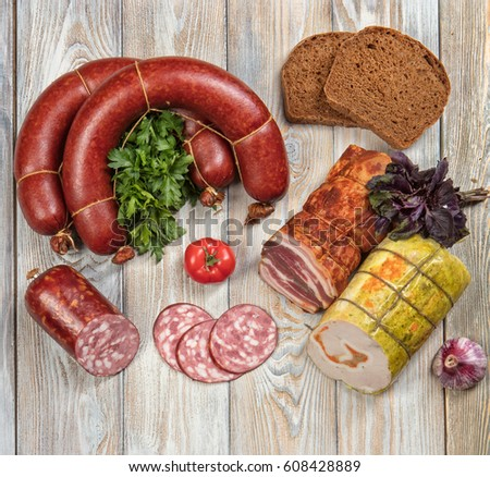 Different kinds of sausages with vegetables on a wooden table