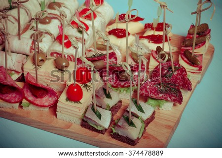 Different kinds of snacks canape on skewers. Selective focus. Toned. - stock photo