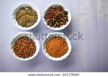 Different kinds of spices in ceramics bowls on wooden background
