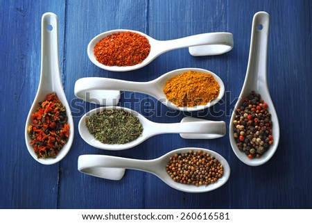Different kinds of spices in ceramics spoons, close-up, on color wooden background - stock photo