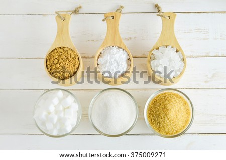 Different kinds of sugar in glass and wooden bowl on white wooden table - brown, white, crystal, cube and Icing sugar - stock photo