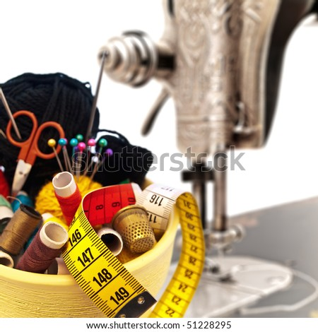 different knitting items in the pot against old sewing machine - stock photo