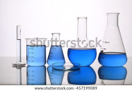 Different laboratory glassware with color liquid and with reflection - stock photo