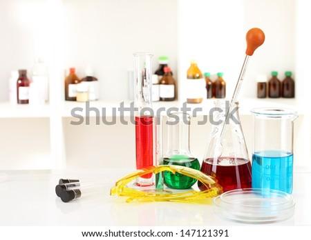 Different laboratory glassware with color liquid on laboratory background - stock photo
