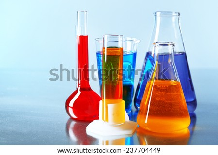 Different laboratory glassware with colorful liquid on color background - stock photo