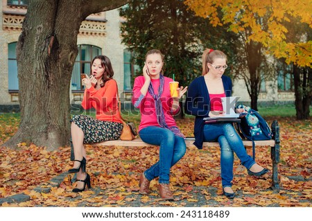 Different lifestyles. Three young women sitting on park bench. One of them doing make up, another gossiping by mobile phone and one studying. - stock photo