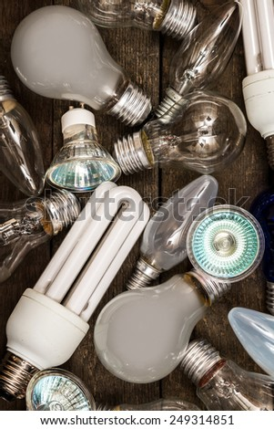 Different lightbulbs on grey background - stock photo
