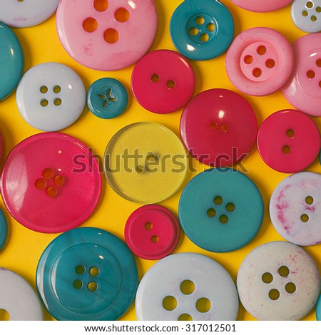 Different many green red and white sewing buttons on a yellow background close up still