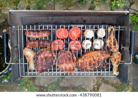 different meat and vegetables on charcoal grill