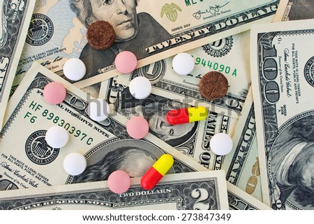 Different medical pills on the background of dollars - stock photo