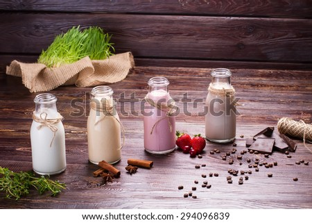 Different milkshakes on the wooden background. - stock photo