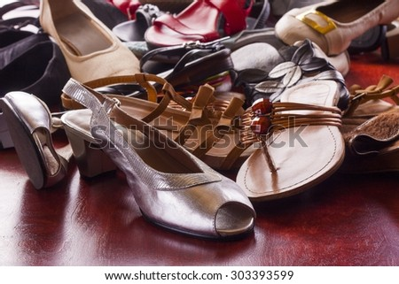 different models of old female footwear over red table - stock photo