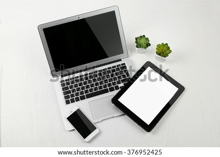 Different modern devices with green plants on light table - stock photo